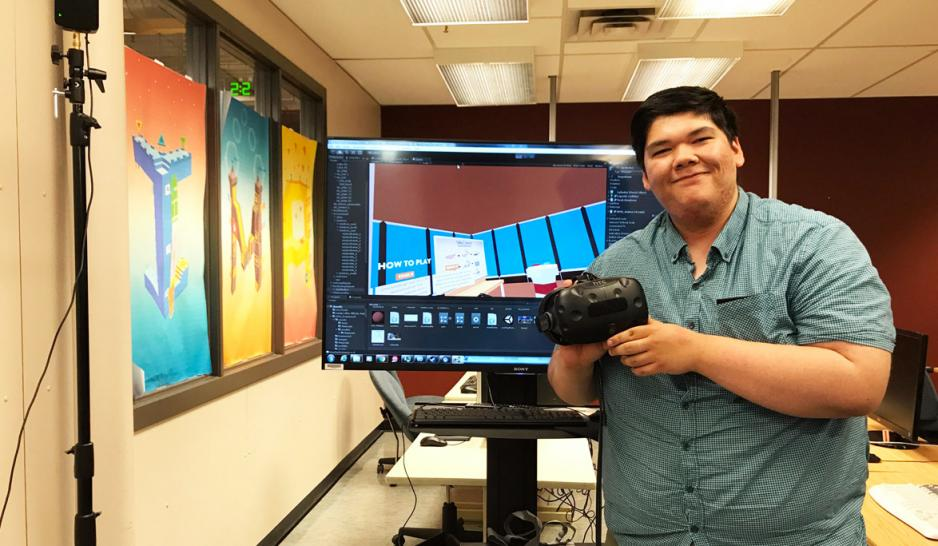 Assiniboine Alumni Dallas Flett-Wapash stands in front of a large TV monitor holding a game controler