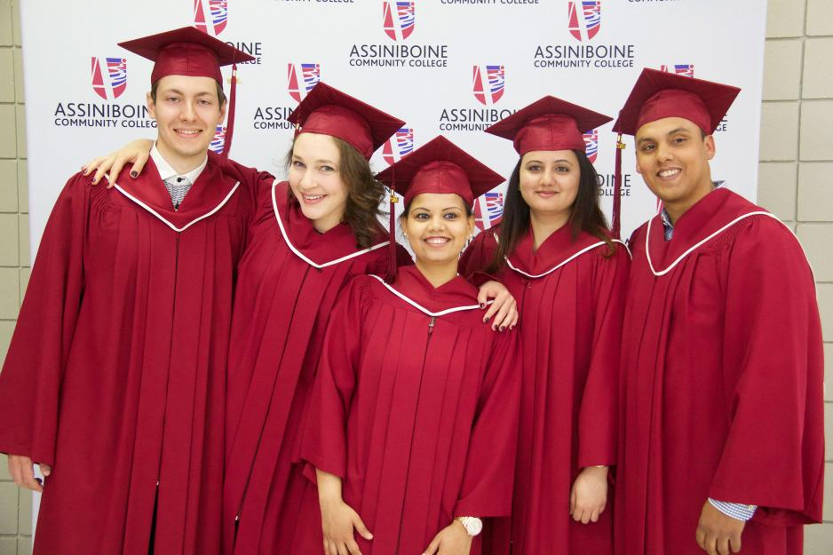 Five students in red graduation caps and gowns stand for a photo.
