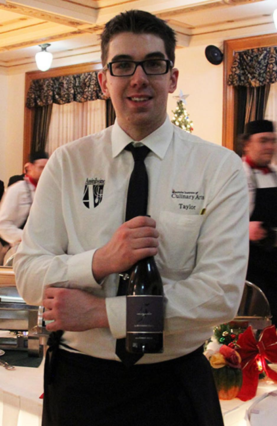 Hotel & Restaurant Management Student stands holding a bottle of wine.