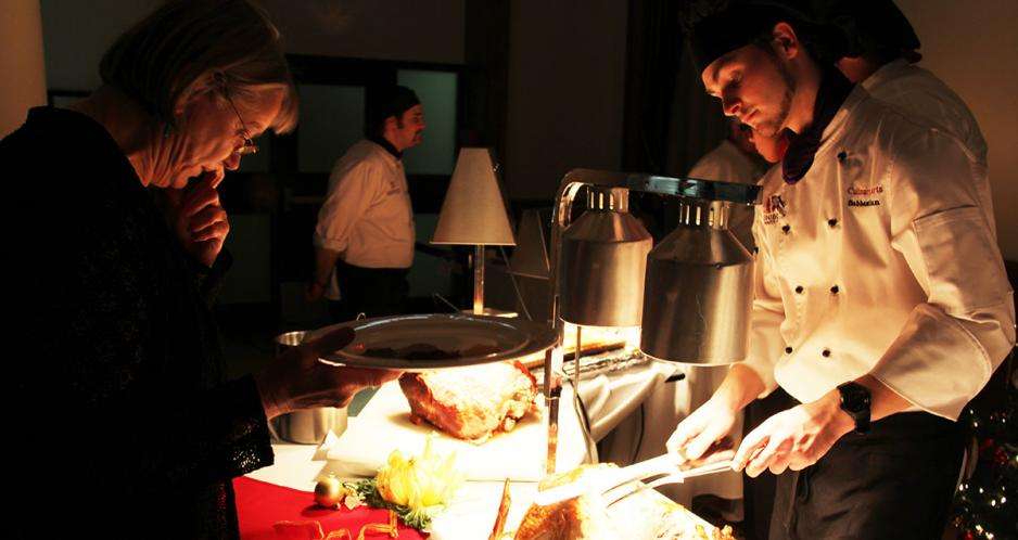 Student carves meat in front of guests at the Holiday Buffet.