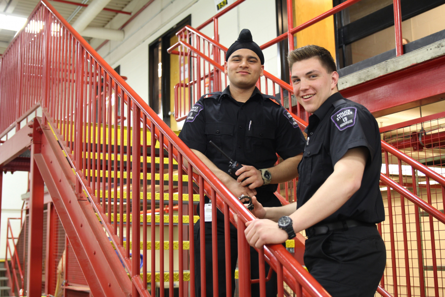 Two police studies students stand on stairs inside the public safety centre