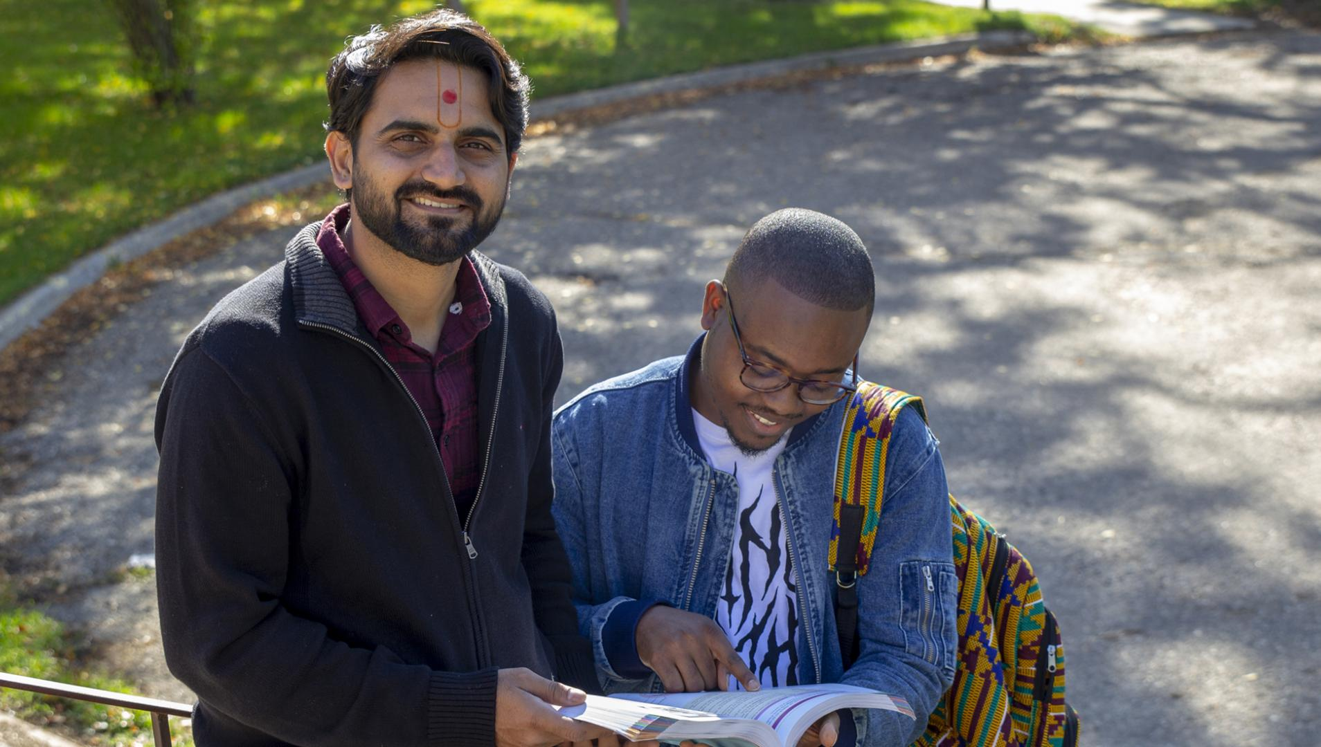 two international students reading a book