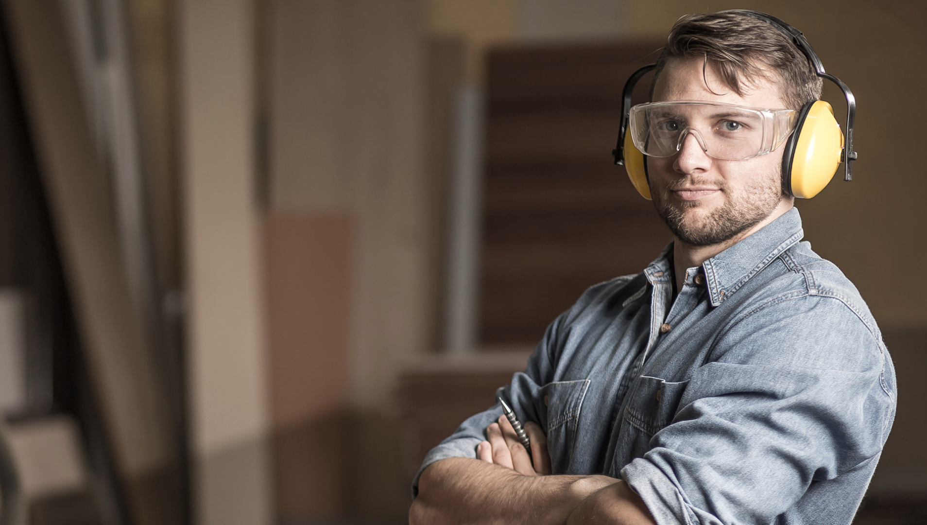 A man with arms crossed while wearing woodworking protective equipment.