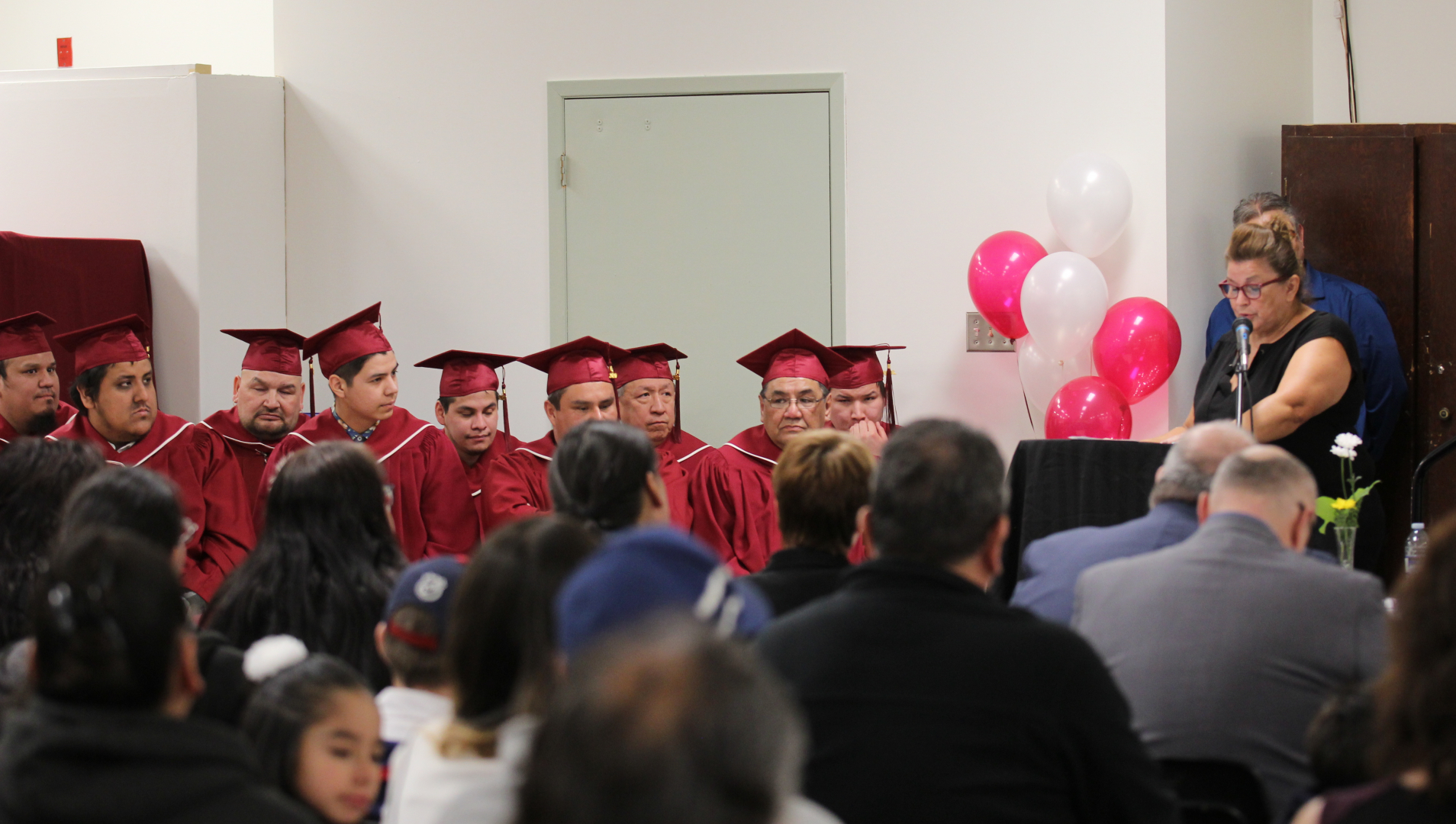 Plumbing graduates listen to a speaker at their graduation ceremony