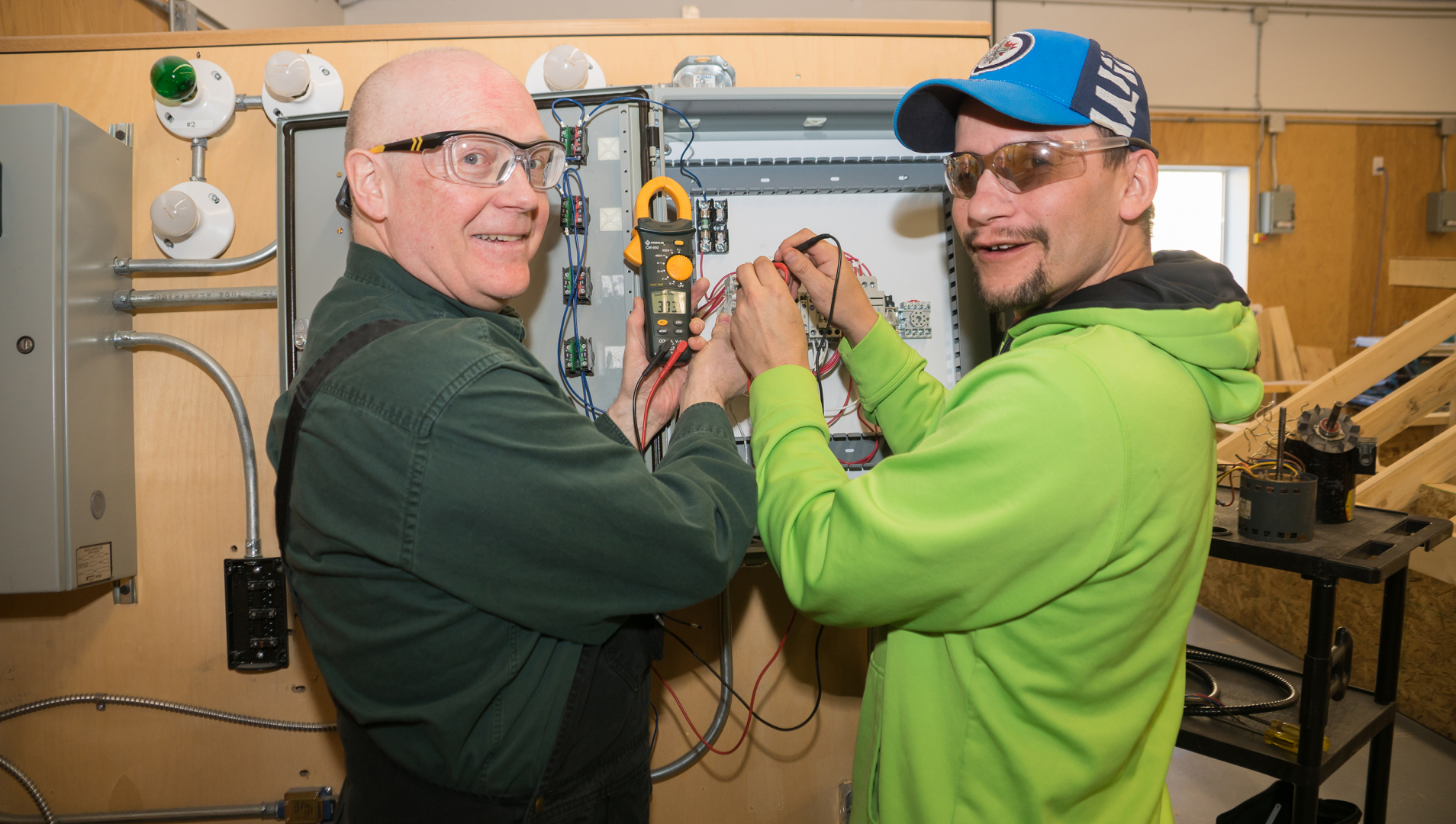 Electrical student and instructor pose while working on wiring.