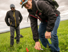An agriculture student smiles while he does experiential work in the field as his instructor watches.