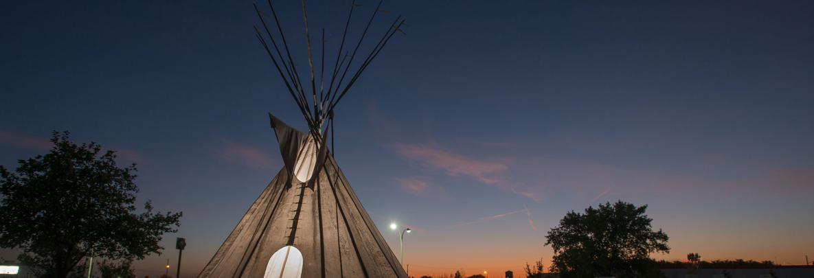 tipi at dusk outside of college's campus