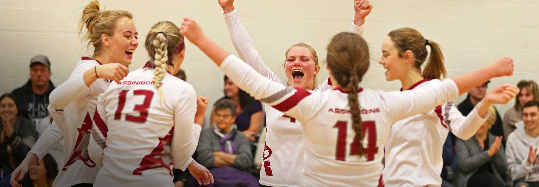 Women's volleyball team celebrates on the court