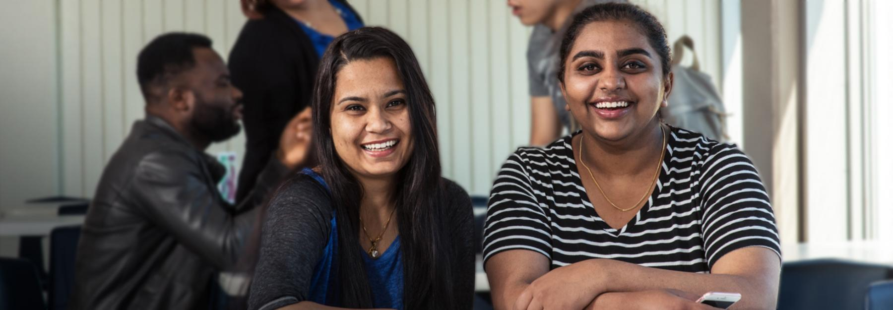 Two female international students looking into camera and smiling while in the college cafeteria