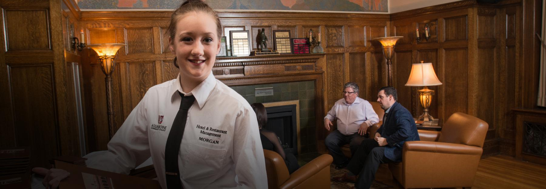 Hotel & Restaurant Management student greets guests at the Great Grey Owl Restaurant